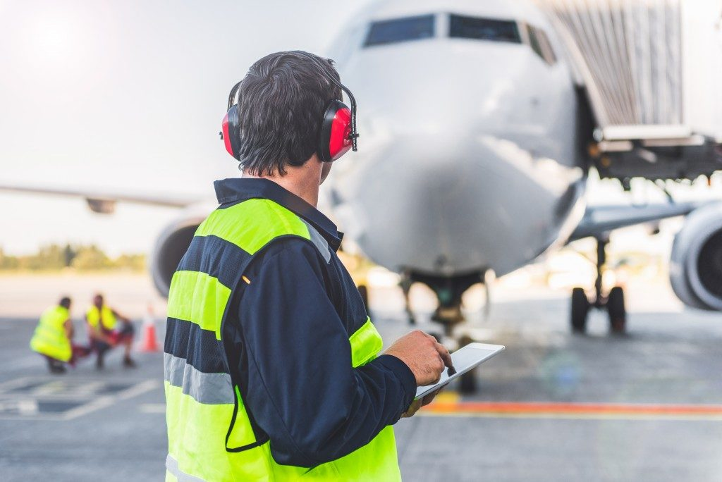 man checking plane requirements for take off