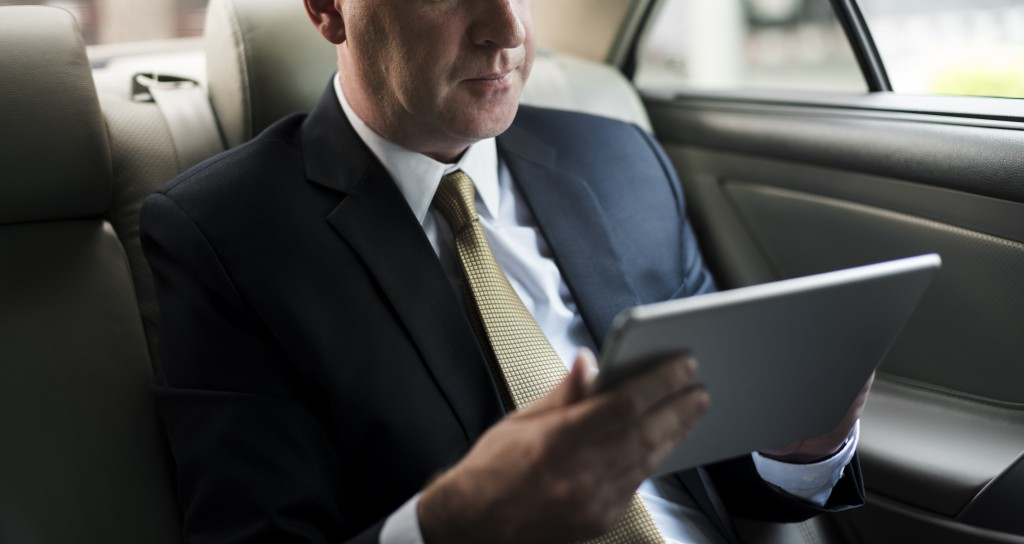 Businessman using his tablet in his car
