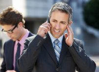 businessman on call covering his ears