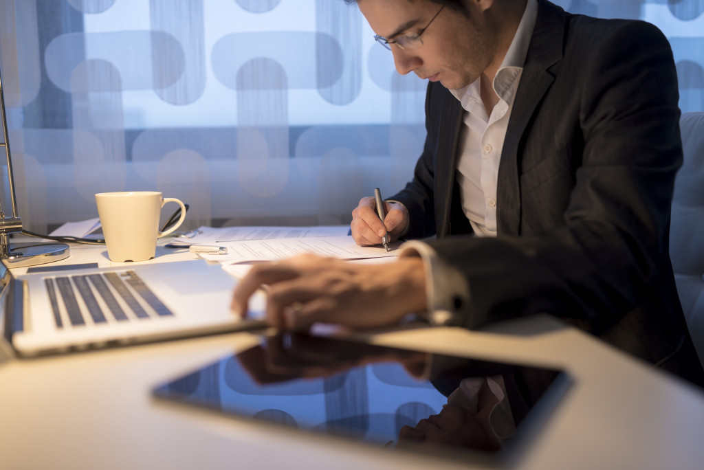 man using computer tablet and a laptop for work